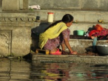 Life is harder here. Women wash their family's clothing by hand in the river.