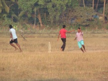 Some kids playing cricket in a field