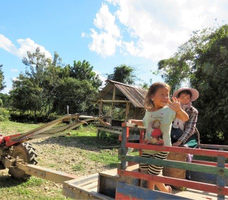 A little girl on a tractor, smiling and waving at us as we passed them on a dirt road