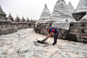 Indonesian workers cover to protect the famed Borobudur temple from volcanic ash from the eruption of Mount Kelud in Magelang, Indonesia, Friday, Feb. 14, 2014. Volcanic ash from a major eruption in Indonesia shrouded a large swath of the country's most densely populated island on Friday and closed three nearby international airports. (AP Photo/Slamet Riyadi)