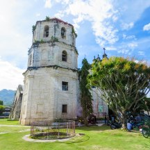 The bell tower is covered in vegetation, giving it an overgrown feel